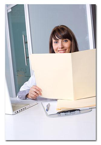 Activites Director reading folder at desk