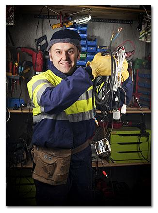 Electrical Contractor holding up wires in a workshop