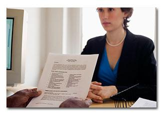 Woman sitting across from desk of someone holding a resume